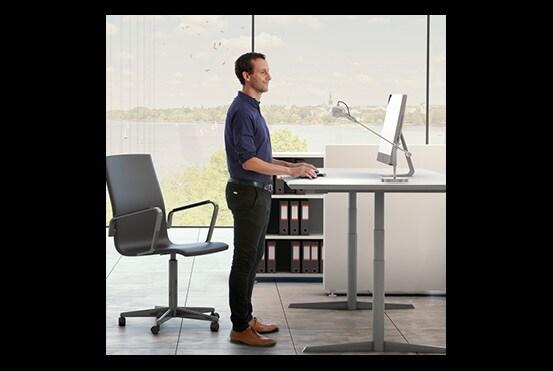Mand stående ved hæve-/sænkebord og kvinde siddende