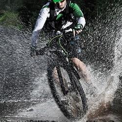 Hard-core mountain biker driving through water