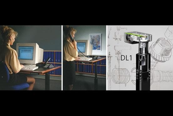 """Administrativní pracovník sedící a stojící u kancelářského stolu. DL1: revoluční """"elektrická noha"""" pro stoly vyvinutá společností LINAK."""