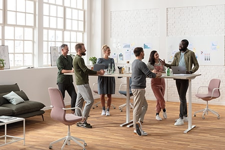 Kantoormedewerkers die aan een ergonomisch en verstelbaar vergaderbureau staan.