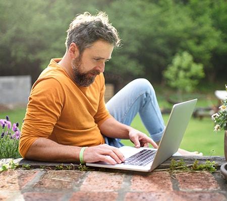 Jonge man met laptop die thuis werkt in de tuin.