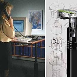 """Employé assis et debout devant un bureau professionnel. DL1: la """"colonne électrique"""" révolutionnaire pour bureaux inventée par LINAK."""