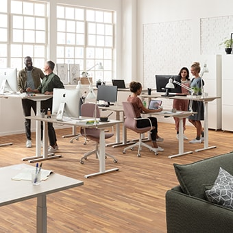 Office workers standing and sitting at ergonomic and adjustable office desks in modern office